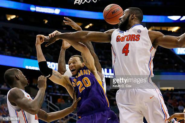 Gary Johnson of the Albany Great Danes goes up for a rebound against Dorian FinneySmith and Patric Young of the Florida Gators in the second half...