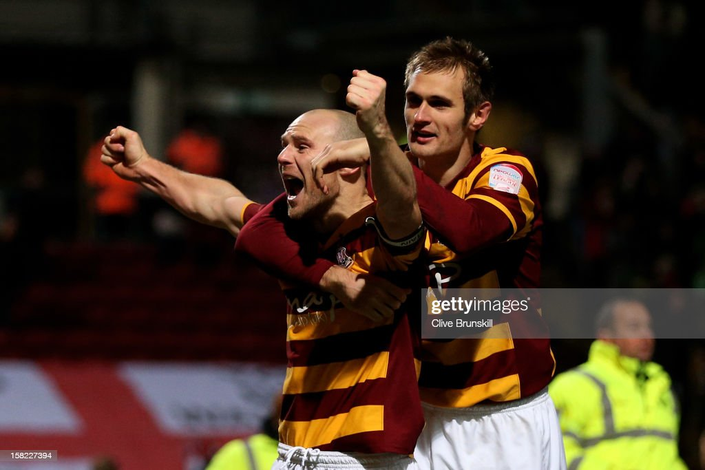 Gary Jones and James Hanson of Bradford celebrate following their team's victory in the penalty shootout during the Capital One Cup quarter final match between Bradford City and Arsenal at the Coral Windows Stadium, Valley Parade on December 11, 2012 in Bradford, England.