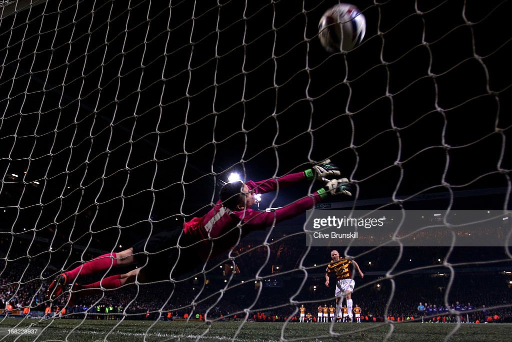 Gary Jones of Bradford scores with his penalty attempt past goalkeeper Wojciech Szczesny of Arsenal during the Capital One Cup quarter final match between Bradford City and Arsenal at the Coral Windows Stadium, Valley Parade on December 11, 2012 in Bradford, England.