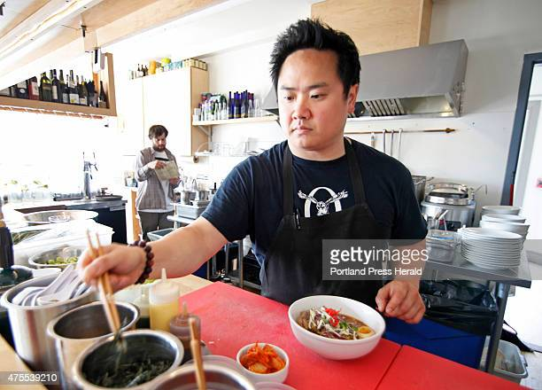 Gary Kim owner of ANJU Noodle Bar in Kittery creates a dish of Shoyu Ramen consisting of MEat bone broth spicy soy tare slowroasted pork shoulder...