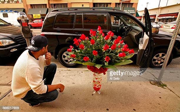 Gary Lee who purchased a huge bouquet of roses in a ornate tall vase tries to figure how he will fit the mass of flowers into his car Lee purchased...