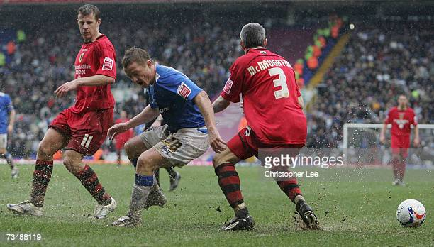 Gary McSheffrey of Birmingham losses the ball in a puddle as he tries to get past Paul Parry and Kevin McNaughton of Cardiff during the CocaCola...