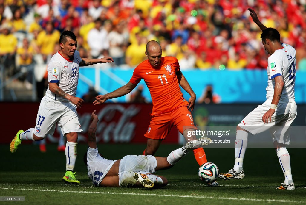 Gary Medel, Felipe Gutierrez and Mauricio Isla of Chile stop the attacking Arjen Robben (#11) of the Netherlands during the 2014 FIFA World Cup Brazil Group B match between the Netherlands and Chile at Arena de Sao Paulo on June 23, 2014 in Sao Paulo, Brazil.