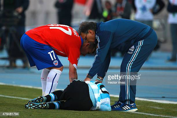 Gary Medel of Chile and Gerardo Martino coach of Argentina help Lionel Messi of Argentina during the 2015 Copa America Chile Final match between...