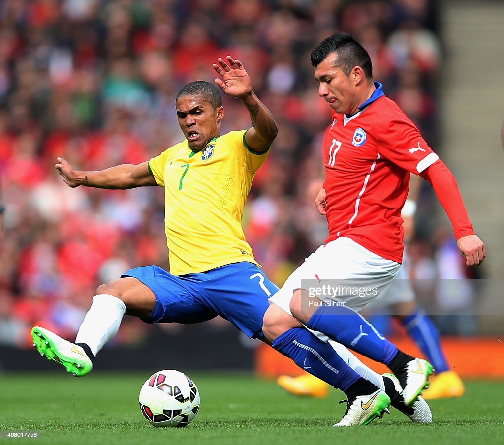 Gary Medel of Chile is challenged by Douglas Costa of Brazil during the international friendly match between Brazil and Chile at the Emirates Stadium...