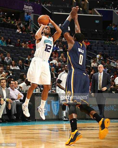 Gary Neal of the Charlotte Hornets shoots against CJ Miles of the Indiana Pacers during the game at the Time Warner Cable Arena on October 23 2014 in...