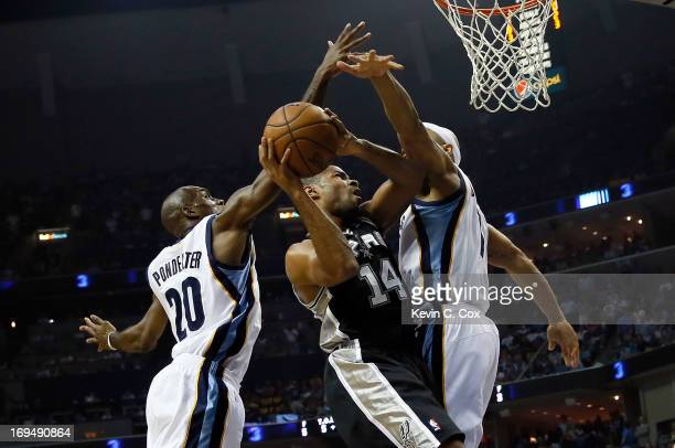 Gary Neal of the San Antonio Spurs goes up for a shot between Quincy Pondexter and Jerryd Bayless of the Memphis Grizzlies in the first half during...