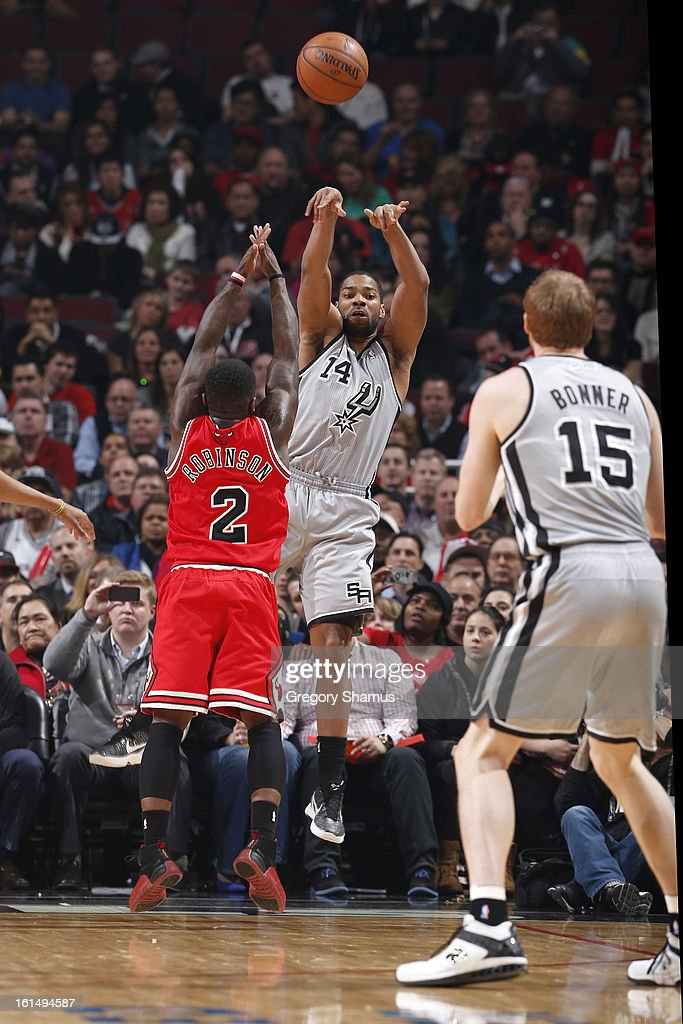 Gary Neal #14 of the San Antonio Spurs passes the ball to teammate Matt Bonner #15 while guarded by Nate Robinson #2 of the Chicago Bulls on February 11, 2013 at the United Center in Chicago, Illinois.