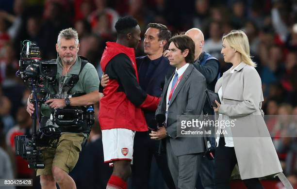 Gary Neville greets Danny Welbeck of Arsenal as Sky Sports television enter the pitch to interview the players after the Premier League match between...