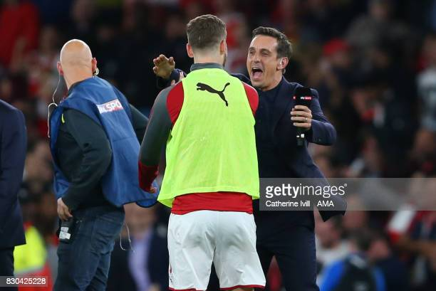Gary Neville greets Shkodran Mustafi of Arsenal as Sky Sports television enter the pitch to interview the players after the Premier League match...