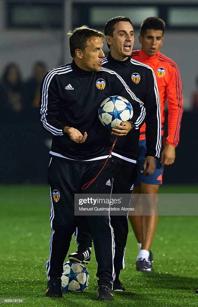 Gary Neville the new manager of Valencia CF and Valencia CF assistant coach Phil Neville (L) give instructions during a training session ahead of Wednesday's UEFA Champions League Group H match against Olympique Lyonnais at Paterna Training Centre on December 07, 2015 in Valencia, Spain.
