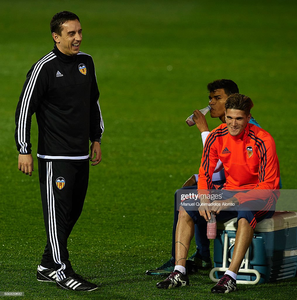 Gary Neville the new manager of Valencia CF reacts with his players Rodrigo De Paul (R) and Danilo Barbosa during a training session ahead of Wednesday's UEFA Champions League Group H match against Olympique Lyonnais at Paterna Training Centre on December 07, 2015 in Valencia, Spain.