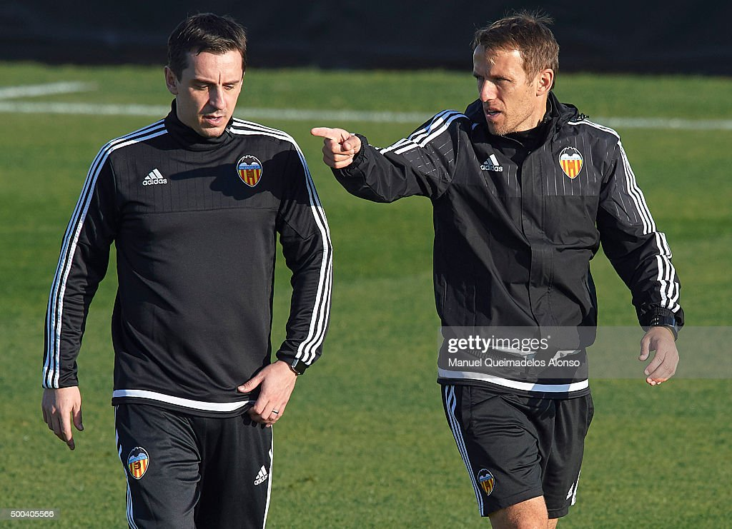Gary Neville (L) the new manager of Valencia CF talks to Valencia CF assistant Phil Neville during a training session ahead of Wednesday's UEFA Champions League Group H match against Olympique Lyonnais at Paterna Training Centre on December 08, 2015 in Valencia, Spain.