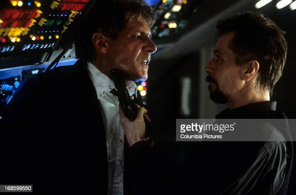 Gary Oldman aiming gun at Harrison Ford in a scene from the film 'Air Force One' 1997