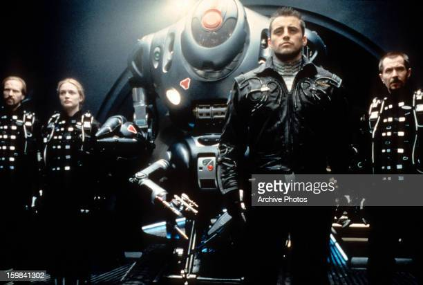 Gary Oldman William Hurt Heather Graham and Matt LeBlanc standing with a space machine in a scene from the film 'Lost In Space' 1998