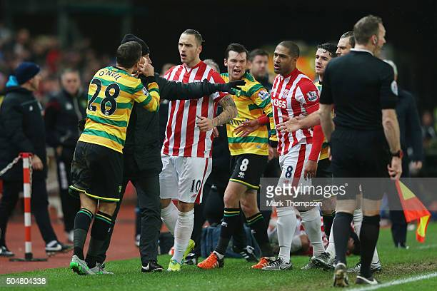 Gary O'Neil of Norwich City faces angry Stoke City players after fouling Ibrahim Afellay of Stoke City during the Barclays Premier League match...