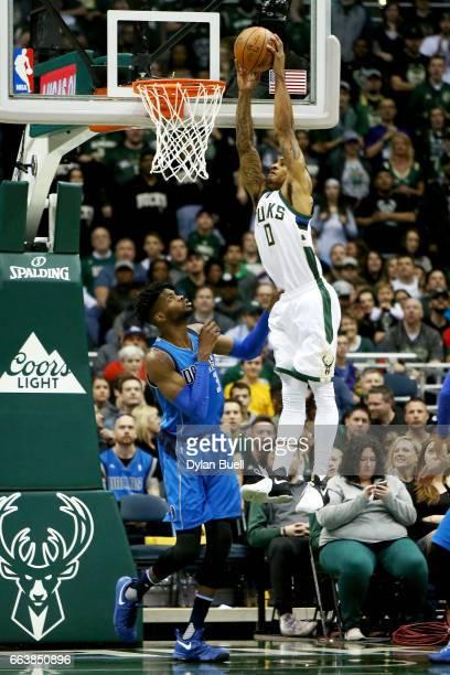 Gary Payton II of the Milwaukee Bucks dunks the ball over Nerlens Noel of the Dallas Mavericks in the third quarter at BMO Harris Bradley Center on...