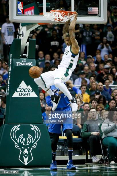 Gary Payton II of the Milwaukee Bucks dunks the ball past Nerlens Noel of the Dallas Mavericks in the third quarter at BMO Harris Bradley Center on...