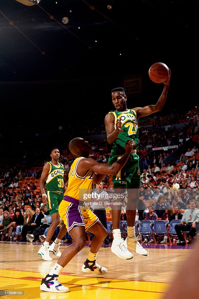 Gary Payton #20 of the Seattle SuperSonics looks to pass the ball against Sedale Threatt #3 of the Los Angeles Lakers during a game played at the Great Western Forum in Los Angeles, California circa 1991.