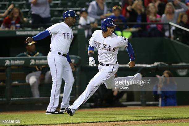Gary Pettis third base coach waves on Leonys Martin of the Texas Rangers rounds third base to score in the eighth inning against the Oakland...