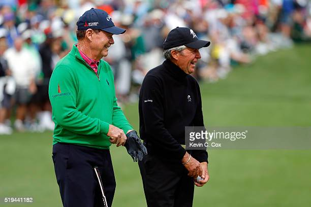 Gary Player celebrates with Tom Watson of the United States after hitting a hole in one on the seventh hole during the Par 3 Contest prior to the...