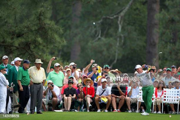 Gary Player hits a tee shot as Jack Nicklaus and Arnold Palmer watch during the Par 3 Contest prior to the start of the 2012 Masters Tournament at...