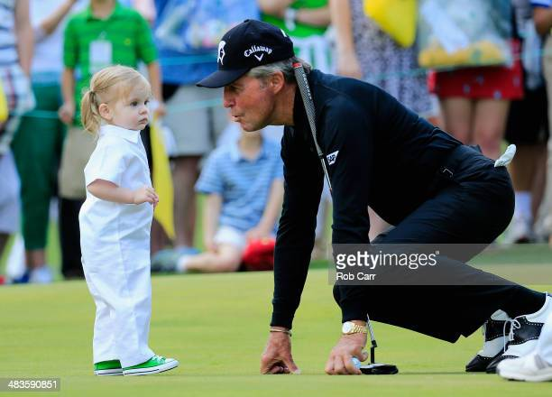 Gary Player of South Africa greets a young caddie during the 2014 Par 3 Contest prior to the start of the 2014 Masters Tournament at Augusta National...