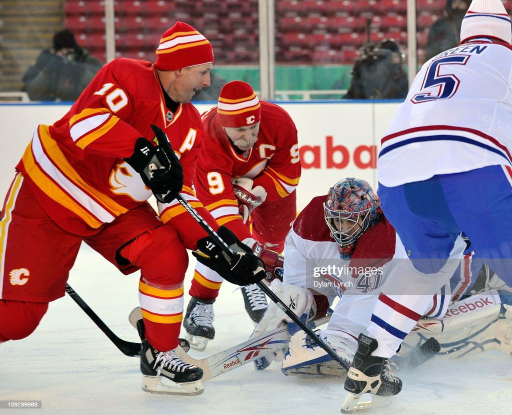 Gary Roberts #10 and Lanny McDonald #9 of the Calgary Flames Alumni attack the net against Eric Fichaud #41 of the Montreal Canadiens Alumni during the Alumni game held as part of the 2011 NHL Heritage Classic festivities at McMahon Stadium on February 19, 2011 in Calgary, Canada.