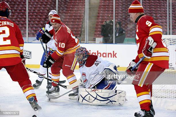 Gary Roberts of the Calgary Flames skates against Eric Fishaud of the Montreal Canadiens during the 2011 Heritage Classic Alumni Game on February 19...