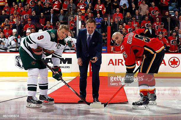 Gary Roberts participates in a ceremonial puck drop before the game with Mark Giordano of the Calgary Flames and Mikko Koivu of the Minnesota Wild at...