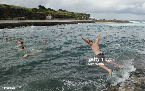 Gary Rohan jumps into the ocean during a Sydney Swans AFL recovery session at Clovelly Beach on April 14 2014 in Sydney Australia