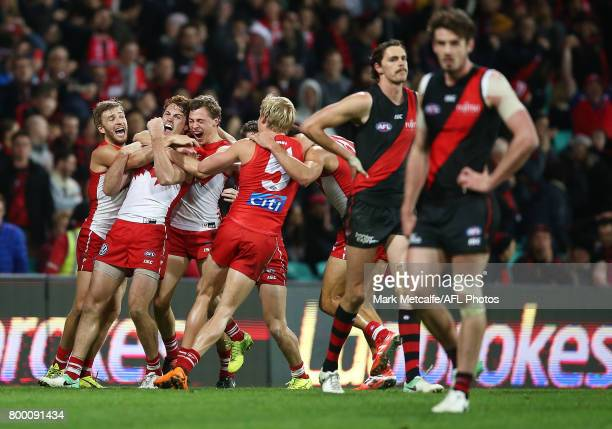 Gary Rohan of the Swans celebrates with team mates after kicking a goal to win the match during the round 14 AFL match between the Sydney Swans and...
