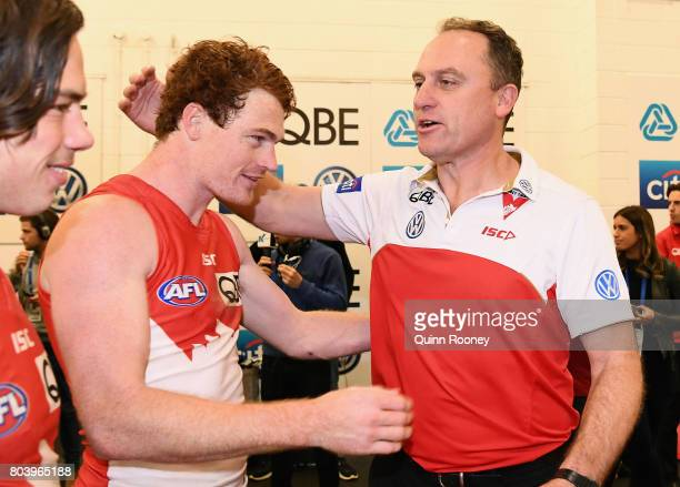 Gary Rohan of the Swans is congratulated by Swans head coach John Longmire in the rooms after winning the round 15 AFL match between the Melbourne...