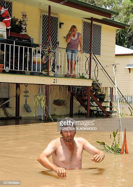 Gary Russell waits for his wife Robyn and dogs to be evacuated by emergency personnel from their flood affected home in Rockhampton on January 6 2011...