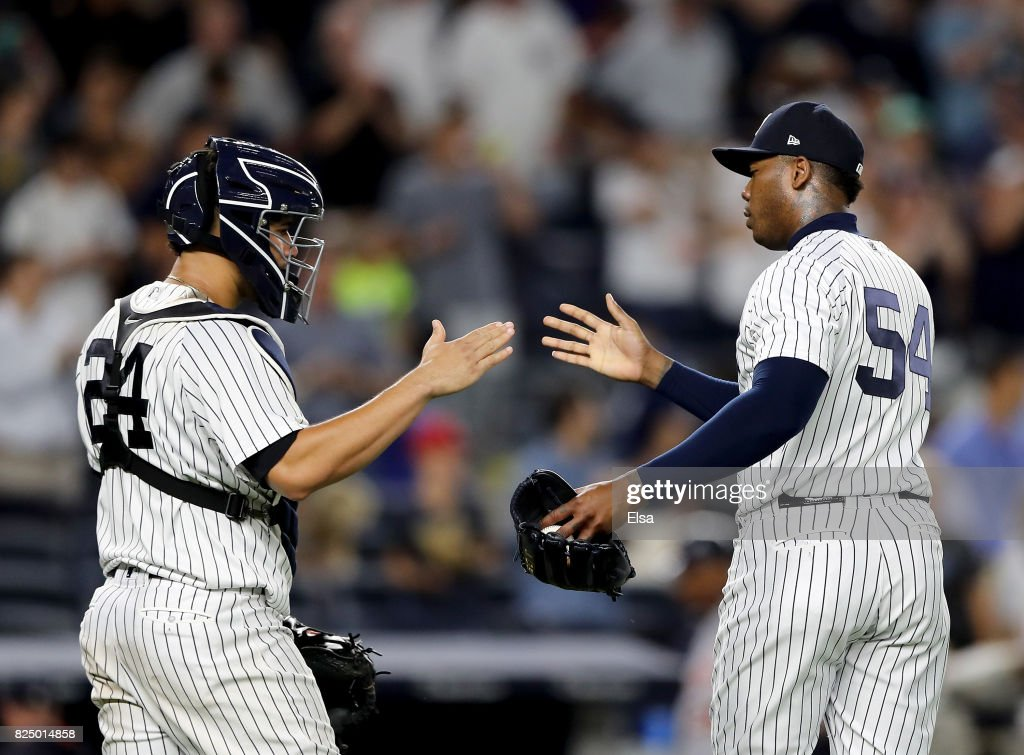 Gary Sanchez #24 and Aroldis Chapman #54 of the New York Yankees celebrate the 7-3 win over the Detroit Tigers on July 31, 2017 at Yankee Stadium in the Bronx borough of New York City.