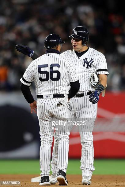 Gary Sanchez of the New York Yankees celebrates with first base coach Tony Pena after hitting a two run double in the eighth inning against the...