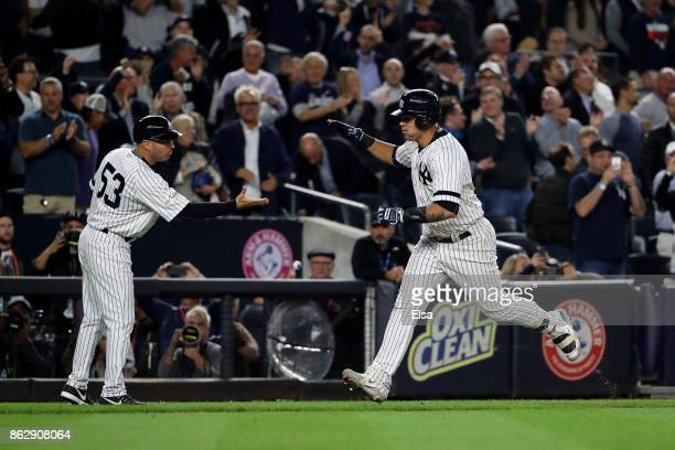 Gary Sanchez of the New York Yankees celebrates with third base coach Joe Espada after hitting a solo home run during the seventh inning against the...