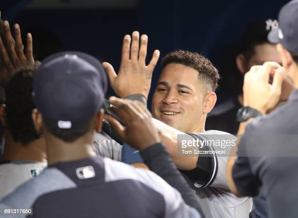 Gary Sanchez of the New York Yankees is congratulated by teammates in the dugout after hitting a tworun home run in the fourth inning during MLB game...