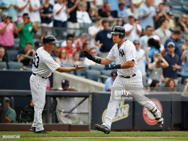 Gary Sanchez of the New York Yankees is congratulated by third base coach Joe Espada after he hit a tworun home run against the Boston Red Sox during...