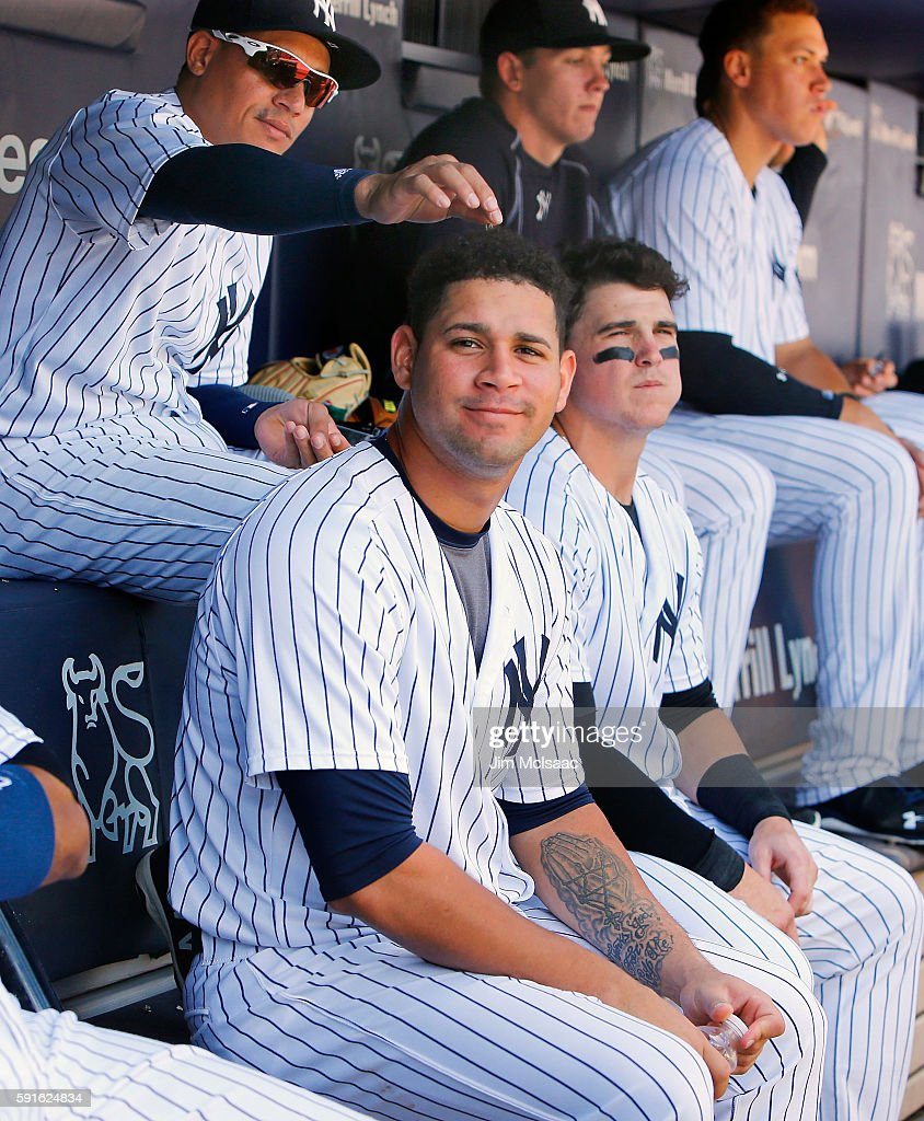 Gary Sanchez of the New York Yankees looks on against the Toronto Blue Jays as teammate Ronald Torreyes places sunflower seeds on his head at Yankee...