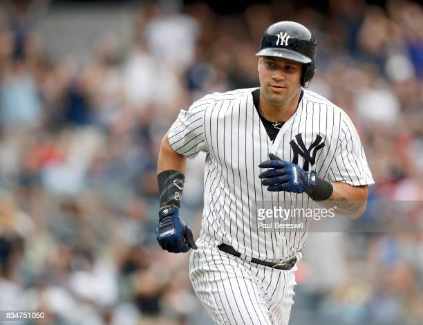 Gary Sanchez of the New York Yankees looks over to teammates in the dugout as he runs up the first base line after hitting a home run in an MLB...