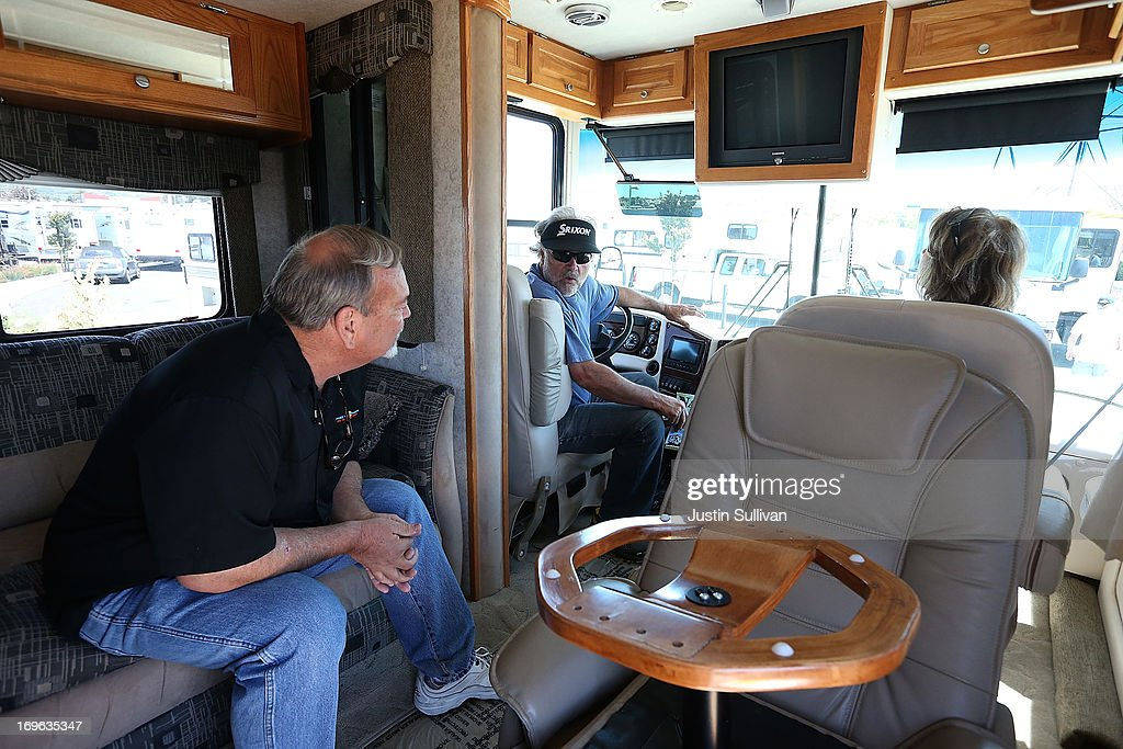 Gary Shelton (C) and his wife Teri Shelton (R) talk with a salesperson while sitting inside of a motorhome at Cordelia RV on May 29, 2013 in Fairfield, California. Deliveries of motor homes and towable RVs to dealers surged 11 percent in the first quarter and the RV industry anticipates a total of 307,300 units will be shipped this year, the highest number since 2007.