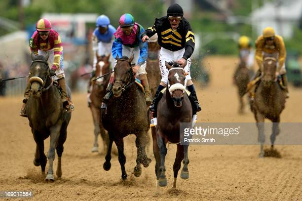 Gary Stevens celebrates atop of Oxbow as he comes to the finish line to win the 138th running of the Preakness Stakes at Pimlico Race Course on May...