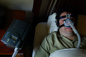 Gary Stewart wears an oxygen type mask hooked to a condenser as he sleeps to treat chronic sleep apnea Tuesday November 5 2002