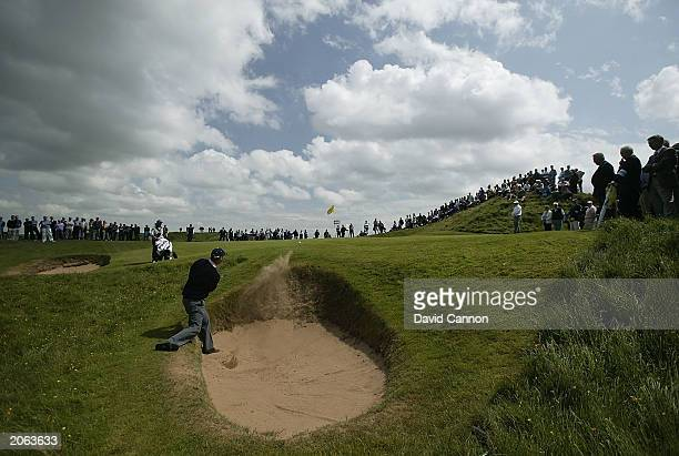 Gary Wolstenholme of England plays a tricky bunker shot to save par at the par 3 'Postage Stamp' 8th hole on his way to beating Raphael De Sousa of...