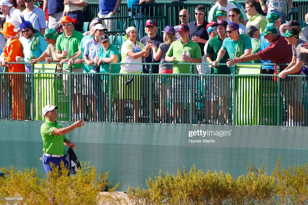 Gary Woodland hands out Under Armour products on the 16th hole during the third round of the Waste Management Phoenix Open at TPC Scottsdale on February 2, 2013 in Scottsdale, Arizona.