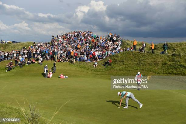 Gary Woodland of the United States picks his ball out of the hole on the 12th hole during the third round of the 146th Open Championship at Royal...