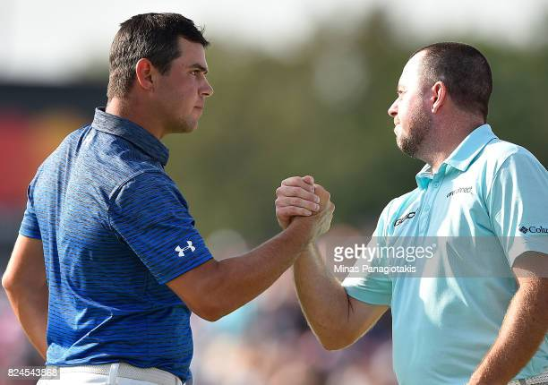 Gary Woodland of the United States shakes hands with Robert Garrigus of the United States on the 18th hole during the final round of the RBC Canadian...