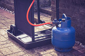 Large blue gas canister attatched to a portable barbecue on wheels in a domestic garden