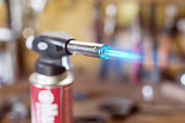 Gas cartridge gun lighter .Close-up nozzle of burner with blue flame jet. Workshop background, scorching of wood.